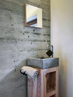 I materiali sono scelti per la loro forza espressiva. Legno naturale e cemento grezzo sono usati anche per il lavandino.
