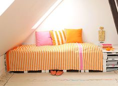 Bedcover / bedspread in orange and offwhite stripes with a stripe of pink and a stripe of orange in each end. Matches the cushions - all designed by kira-cph.com