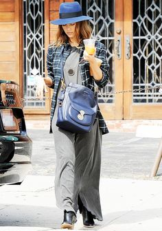 Jessica Alba wears a maxi dress, plaid shirt, gold pendant, blue fedora, matching bucket bag, and ankle boots