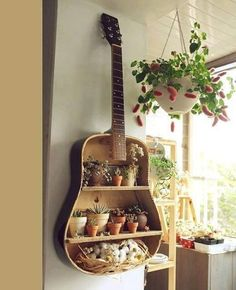 A salvaged guitar is turned into a wall plant holder!