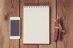 Blank notepad with smart phone and pencils on wooden table. View from above