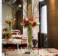 The couple placed tall glass vases filled with orange, gold and red flowers and long branches of curly willow on some tables, and smaller square vases with the same blooms on others. Alternating high and low centerpieces highlighted the drama of more the elaborate arrangements without overwhelming their overall look (and budget!).