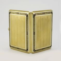 A Fabergé gold and enamel cigarette case, workmaster Henrik Wigström, St Petersburg, circa 1908-1917. The rounded rectangular case engraved with alternating engine-turned patterns within a border of black champlevé enamel relieved by a laurel wreath pattern, all within a border of white opaque enamel, with collet-set cabochon sapphire pushpiece.