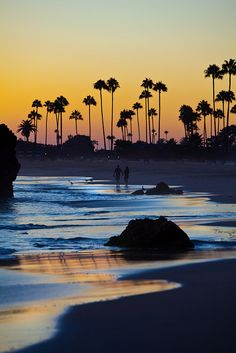 A young couple walking the coastline enjoying a beautiful sunset in Corona Del Mar California.