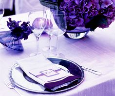 Rich plum centerpieces, napkins and menu cards work luxuriously with lighter, periwinkle table linens