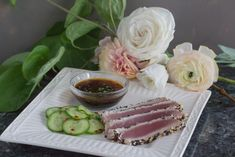 Monash University Certified Low FODMAP Sesame Crusted Tuna & pickled cucumbers sliced and laid out on a white square plate with dipping sauce.