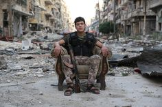 """The sons of war: Syria's refugees  –  in pictures. """"A young soldier from the Free Syrian Army sits among the rubble in a street in Salahuddin, Aleppo. All Photographs: Gabriel Chaim"""