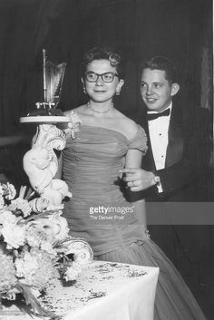 DEC 6 1955; Examining a tiny harp, one of the gold musical instruments that were part of the Emerald room decorations at the Symphony Jewel ball, are the Donald Bromfields Jr.;