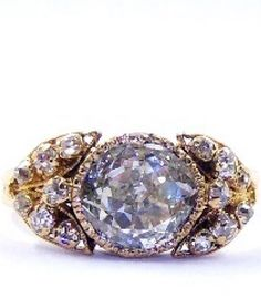 A rare and important Georgian diamond ring, circa 1820. Mounted to the centre with an early cushion cut diamond, approximately one carat, the shoulders formed of stylised leaf motifs and set with old cut diamonds. Handcrafted in 18 carat yellow gold.