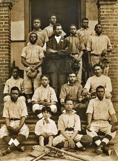 Young African American baseball team, and possibly coach, posing on front steps of building*Year Unknown*