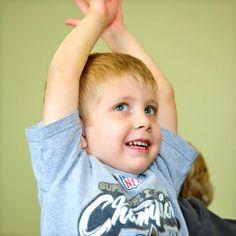 Preschool boy raising his arms