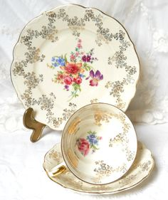 Lovely footed vintage tea cup trios decorated with flowers and gold trimming on off white porcelain. Marked Edelstein, Bavaria. Made in Germany between 1931 and 1974, probably in the forties.  It is in very good condition, no chips or cracks. Beautiful!  Please do not put it in the dishwasher! 927  We have a matching tea and coffee set, and a cake plate listed in our shop.  For more vintage items please visit our shop: http://www.minoucbrocante.etsy.com  For combined shipping please contact…