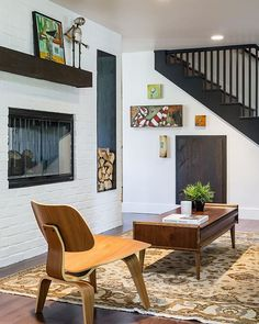 The living room of  Gilham remodel that was completed in July. A double sided wood burning fireplace surrounded by white painted brick, a steel lined box for firewood, and mantel wrapped with reclaimed wood. #jordaniversonsignaturehomes