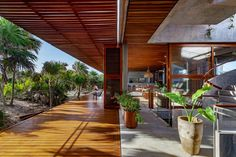 A patio wraps around almost the entire first storey of this house and has floors covered in locally sourced wood. A wood roof above shades numerous places to sit and lounge outside Jacuzzi, Tulum, House Cast, Timber Pergola, Camas King, Beachfront House, Storey Homes, Rooftop Pool, Los Angeles Homes