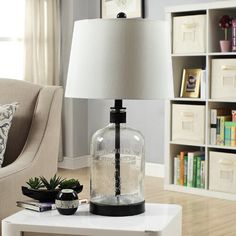The Woodburn clear glass table lamp accented with black metal details. The hardback tapered drum shade has a white silk fabric measuring 12 x 14 x Table Lamps For Bedroom, Metal Table Lamps, Black Table Lamps, Clear Glass Table Lamp, Lamp Table, Fabric Shades, Lamp Shades, Farmhouse Lamps, Modern Farmhouse