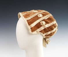 1802- a well-preserved American example of early 19th century headwear, this bonnet typifies a classic high-style shape of the period. The rich velvet and silk ribbon used would perfectly suit a formal evening ensemble, as opposed to the lighter cottons and linens frequently used in day bonnets and caps. (side view)