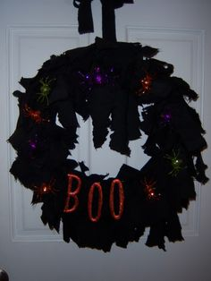 "Like this home-made wreath!!    ""Finally finished up my wreath today........the spiders are clip on glitter spiders from Michaels, so I can rearrange them according to whim!!  Pic is a bit dark, the spiders are a bit more glittery.......fabric is some old curtain just cut into strips & tied onto a foam wreath spray painted black!"""
