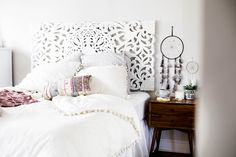 Urban Outfitters bedroom with Magical Thinking Pom-Fringe Duvet Cover and Agda Printed Yarn Pillow and Sienna Headboard and west elm side table