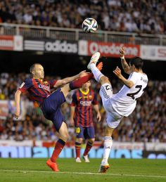 Andres Iniesta (L) of FC Barcelona battles for the ball against Angel Di Maria of Real Madrid during the Copa del Rey Final between Real Madrid and Barcelona at Estadio Mestalla on April 16, 2014 in Valencia, Spain.