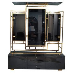 Monumental two piece 1970s impressive enclosed brass display cabinet/sideboard by Guy Lefevre. Top tier structure in square brass tubing, black lacquered wood with doors and shelves in smoked glass. Bottom tier sideboard in black lacquered wood. The upper tier with a central rectangular display shelf, flanked by two smaller side display shelves with glass doors. The lower tier has three central drawers flanked by cupboards.  Good original condition. Wear consistent with age and use. Minor…
