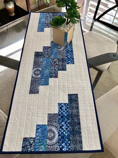 This is a beautiful handmade, reversible, quilted table runner that measures 16 1/4 x 40 1/4. The top features 100% cotton of various shades of blue and white. The white on white background has a starburst design in the center of a small square. The border is the same white on