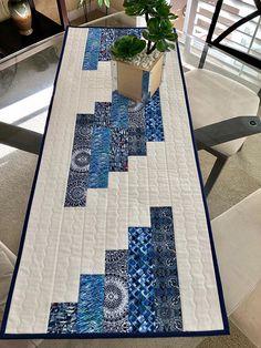 Este es un hermoso cuadro hecho a mano, reversible, acolchado que mide 16 1/4 x 40 1/4. La parte superior cuenta con 100% algodón de distintos tonos de azul y blanco. El blanco sobre fondo blanco tiene un diseño de starburst en el centro de una pequeña plaza. La frontera es el