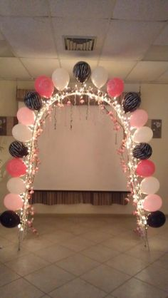 This arch decoration is a very good idea, especially if twinkle lights and flowers were added in the same color palette around the party area, and the balloons were a cream-colored and pale pink, instead of the colors chosen here