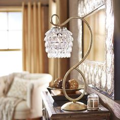 Romantic, Victorian-inspired lighting—with a modern twist. This sculpted golden and faux crystal lamp adds a dazzling touch to any room.