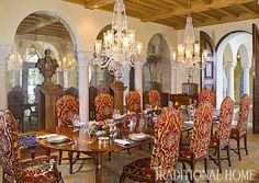 Mirrored walls in the formal dining space reflect the glamour of crystal chandeliers, nailhead-trim upholstered chairs, and a hand-stenciled sisal carpet. - Photo: Carmel Brantley / Design: Frank de Biasi