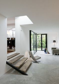 Living space with concrete floor and reclaimed wood stairs. House Arabellagasse by SUE Architekten. Photo by Hertha Hurnaus.