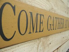 COME GATHER AT OUR TABLE    A nice addition to your dining area.  This sign is 5 x 48 and shown in Mustard with Black lettering.    THIS SIGN IS
