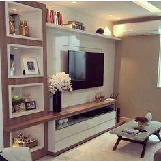 Sala de TV com nichos iluminados em laca branca na estante. O uso do amadeirado trouxe mais cor e acolhimento ao ambiente. Projeto autor desconhecido