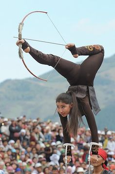 A girl in traditional dress performs archery tricks