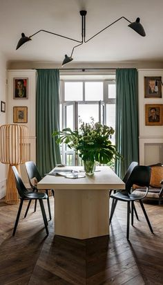 House tour: a 1930s Parisian-style apartment in Warsaw: In the dining room, black plywood chairs by VITRA; three-arm ceiling light by SERGE MOUILLEs; dining table, sideboard and steel lamp with exposed bulb all by Chrapka and her design team; floor lamp (at left) sourced on eBay; a French-style chair (at right) re-purposed into a unique dog bed.