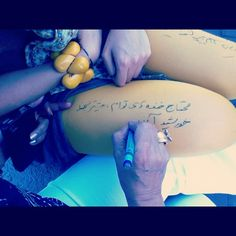 A mother is writing on her daughter's leggings:  a romantic Persian poem which reads: I need your smiles, smile more...