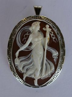 Carved Shell Cameo Depicting A Greek Goddess With A Staff In One Hand And Mirror In The Other, The Full Body Cameo Of A Female Figure With A Flowing Dress Is Set In An 18k White Gold Filigree Surround, Hinged Pin On Back To Wear As A Brooch Or Pendant