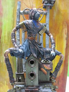 paverpol figure sitting on a birdhouse, brass and metal accents to create a humourous effect