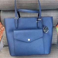 Large leather travel tote There are honestly no words to describe this beauty! This rich, deep blue bag is your perfect travel companion, this bag has 3 different compartments to store all your necessary items, the front pocket holds 8 credit cards. This is the perfect travel or every day bag. Michael Kors Bags Travel Bags