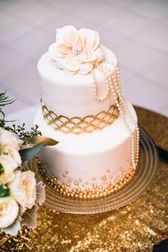 Gold and ivory wedding cake with pearl detailing.