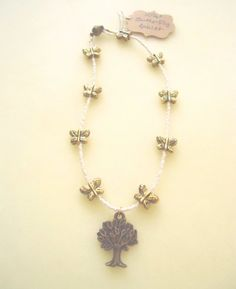 Oodles and oodles of butterflies!  This beautiful anklet (ankle bracelet) is hand-crafted to order, from white / ivory-colored glass and a riot of gold-plated butterfly fittings, accented by an elegant, antiqued brass tree of life charm.  Enjoy :)