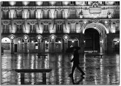 Hombre con paraguas caminando en plaza mayor de Salamanca de noche