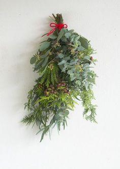 DIY初心者さんにおすすめなドア飾り「スワッグ」。スワッグとは、伝統的なクリスマス飾りのひとつです。ここ数年、日本でも人気になっていますよね。ドイツ語で「壁飾り」という意味を持つスワッグは、材料を束ねて吊るすだけというとってもシンプルで簡単なドア飾りです。 Christmas Swags, Holiday Wreaths, Holiday Decor, Flower Cafe, Handmade Ornaments, Green Flowers, Xmas Decorations, Xmas Tree, Flower Arrangements