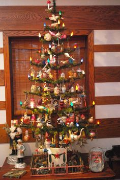 Antique feather tree, decorated with antique ornaments. Surrounded by antique old St Nicks.
