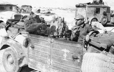 Soldiers eating rations in their Kubelwagon. Note the palm tree/swastika stencil on the door.
