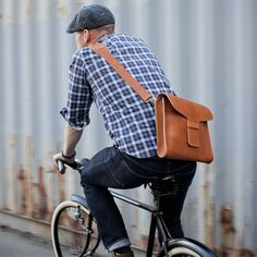 Shop this look on Lookastic:  http://lookastic.com/men/looks/brown-messenger-bag-charcoal-flat-cap-navy-and-white-longsleeve-shirt-charcoal-jeans/4769  — Brown Leather Messenger Bag  — Charcoal Flat Cap  — Navy and White Plaid Long Sleeve Shirt  — Charcoal Jeans
