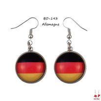 Boucles d'oreilles pendantes drapeau de l'Allemagne. Dimensions: 4,8x2,2cm. Crochets argentés. Le drapeau est recouvert d'un dôme en verre.