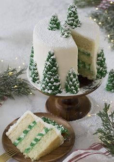 A photo of a christmas tree cake covered in buttercream pine trees and dusted with powdered sugar