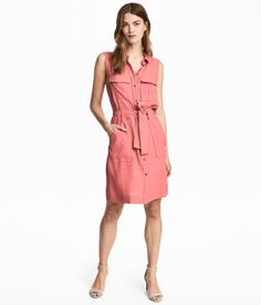 Pink. Straight-cut, sleeveless shirt dress in crêped, woven fabric. Collar, buttons at front, chest pockets with flap, and patch pockets at hem. Tie belt at