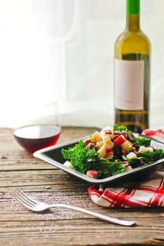 Kale salad with honey apple cider vinaigrette garnished with cranberries, roasted hazelnut and apple.