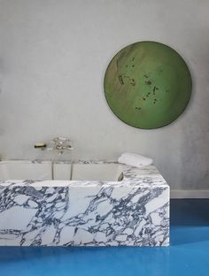 A marble tub surround adds luxurious texture to a modern bathroom from Architectural Digest.